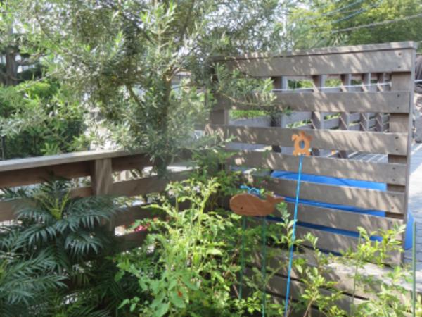 色合いが変化してきた天然木ウッドデッキ、芝生の緑とピンク乱形石とも調和|東京都A様邸
